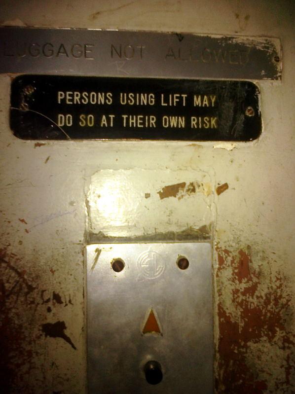 """Tabliczka przy windzie """"Osoby używające windy mogą to robić na własną odpowiedzialność"""" (Mumbaj 2011 r.)"""