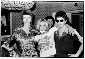 """The Unholy Trinity. MainMan impresario Tony DeFries (rear) laughs on as Ziggy, Iggy, and Lou provide a crash-course in raving at London's Dorchester hotel, 16 July 1972."""